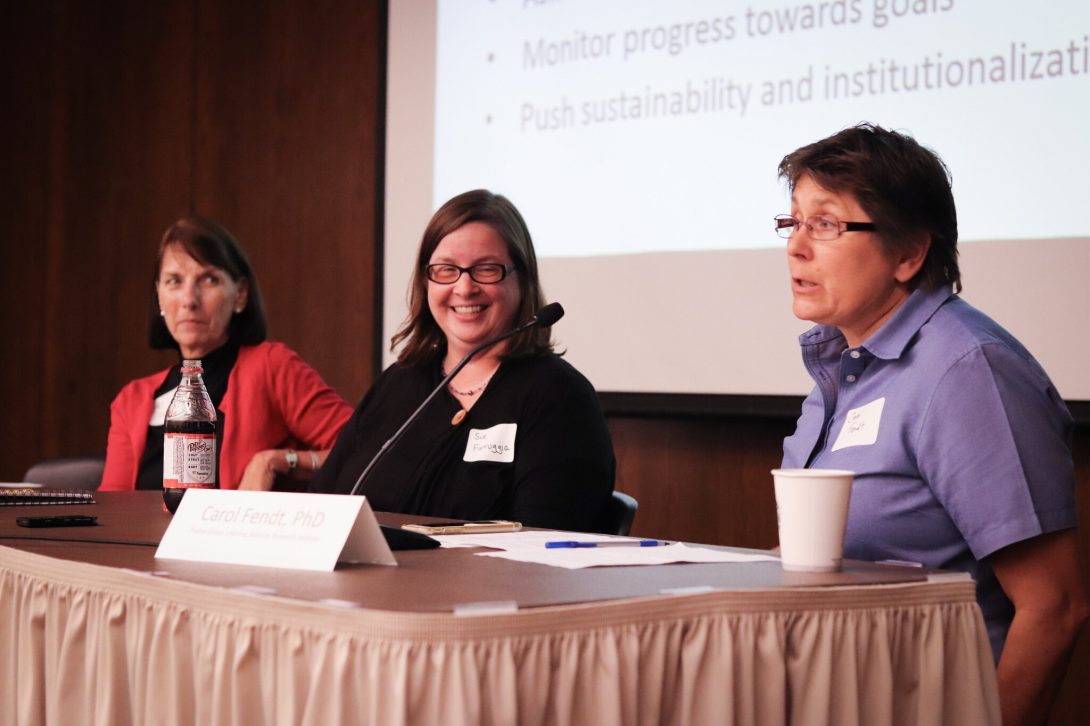 Panelists Carol Fendt, Sue Farruggia and Pat Inman sitting on stage