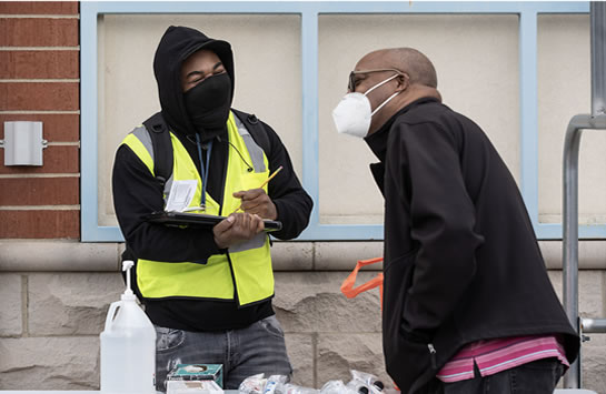 Armani Lee, a COVID outreach supervisor, talks to a Mayfair resident outside the neighborhood Petco on Wednesday, April 21, 2021, in Chicago, Ill.